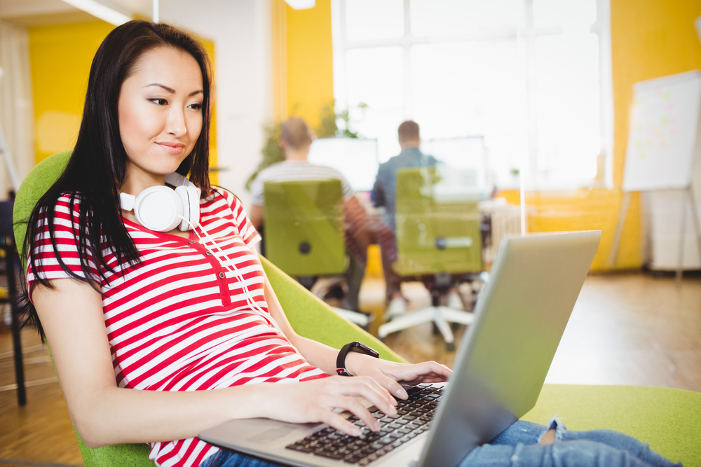 Happy young female executive using laptop at creative office